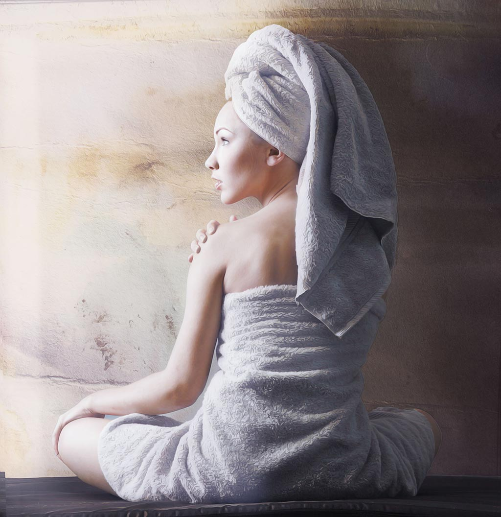 young lady sitting wrapped in towels